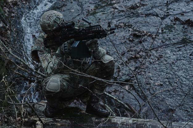 숲에서 기관총으로 전문 장비에 airsoft 선수의 초상화. 전쟁에서 무기를 든 군인