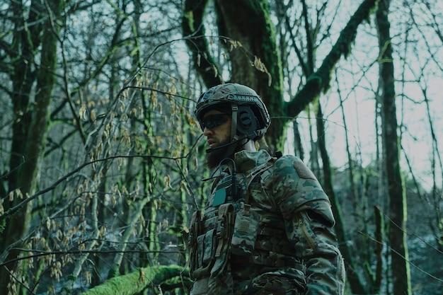 숲에서 기관총을 가진 전문 장비에 있는 airsoft 선수의 초상화. 전쟁에서 무기를 든 군인