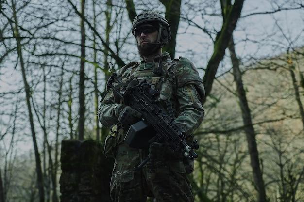 Портрет страйкбола в профессиональном оборудовании с пулеметом в лесу. солдат с оружием на войне