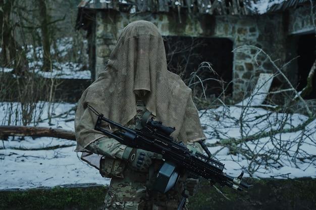 숲에서 기관총 전문 장비에 airsoft 선수의 초상화.