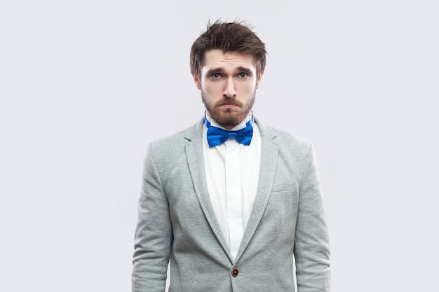 カジュアルな灰色のスーツと青い蝶ネクタイで立って、悲しい目でカメラを見ている一人のハンサムなひげを生やした男の肖像画。明るい灰色の背景に分離された屋内スタジオショット。