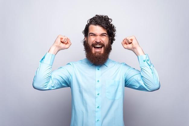 Портрет удивленного и счастливого человека в голубой рубашке празднует победу. цель.