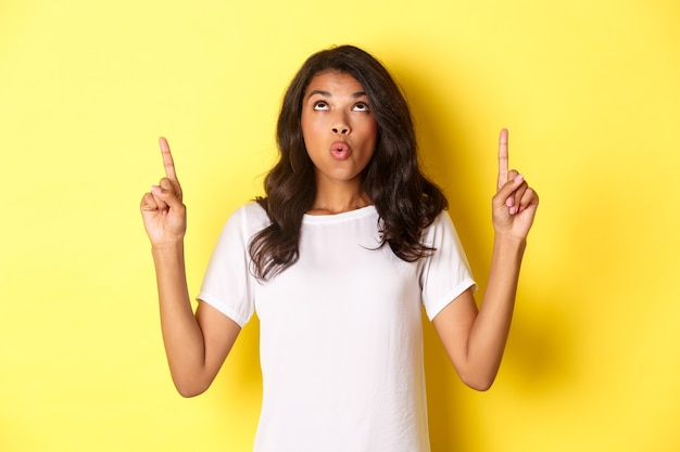 Портрет удивленной и удивленной афро-американской девушки, говорящей вау, указывая и смотрящей на крутой баннер предложения, стоящего на желтом фоне.