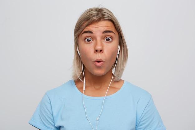 イヤホンで驚いた驚愕の金髪の若い女性の肖像画は青いtシャツを着て唖然とし、白い壁に隔離された音楽を聴いているように見えます