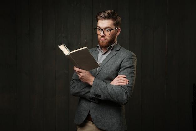 Портрет удивленного случайного человека в очках, читая книгу, изолированную на черном деревянном фоне