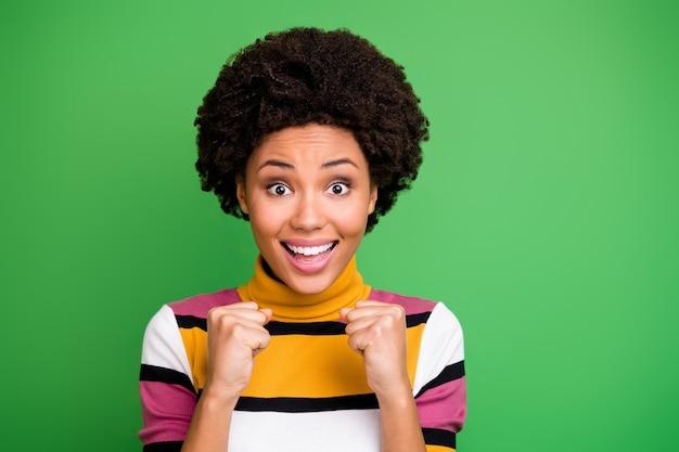 驚いた陽気なアフリカ系アメリカ人の女の子の肖像画は、希望を期待する成功を期待する勝利達成ニュースに感銘を受けた拳を上げる悲鳴を上げる流行の服を着る