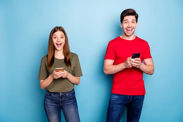 Портрет удивленных сумасшедших, двое женатых людей используют смартфон, читают в социальной сети, впечатлены, как невероятная обратная связь, носят зеленую футболку, джинсовые джинсы, изолированный синий цвет фона