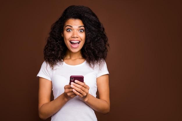 驚いた興奮したアフリカ系アメリカ人の女の子の肖像画は携帯電話を使用してソーシャルメディアのニュースを読んで感動した悲鳴を上げるすごい流行の服を着る。