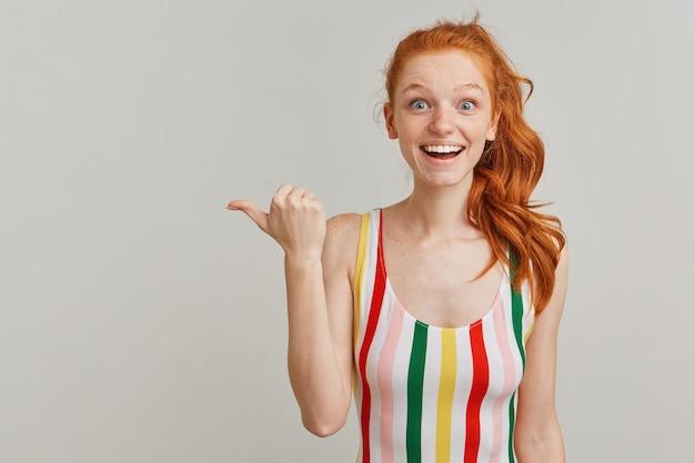 縞模様のカラフルな水着を着て、生姜のポニーテールとそばかすを持つ驚いた女の子の肖像画