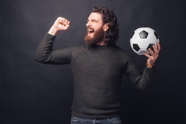 Портрет изумленного красивого бородатого мужчины в непринужденной обстановке держит футбольный мяч и празднует победу