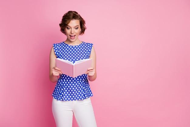Портрет удивленной, впечатленной довольной девушки, читающей заметки с открытым ртом