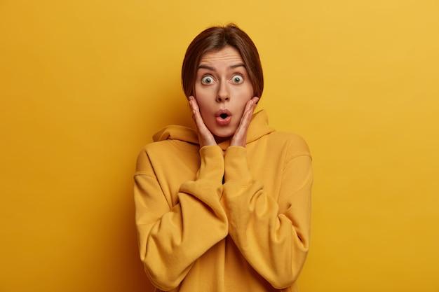 Портрет изумленной миллениальной женщины-модели хватает лицо, смотрит выпученными глазами, видит что-то потрясающее, слушает потрясающую шокирующую историю, позирует в желтом, одетая небрежно. омг, правда