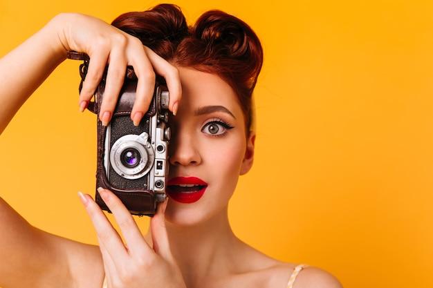 カメラを持つ驚いたピンナップ女性の肖像画。写真を撮る赤い唇を持つ魅力的な写真家。