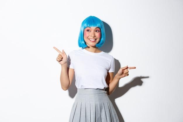 Портрет изумленной улыбающейся женщины в синем парике, одетой для празднования хэллоуина, указывая пальцами в сторону, показывая две промо, стоя.