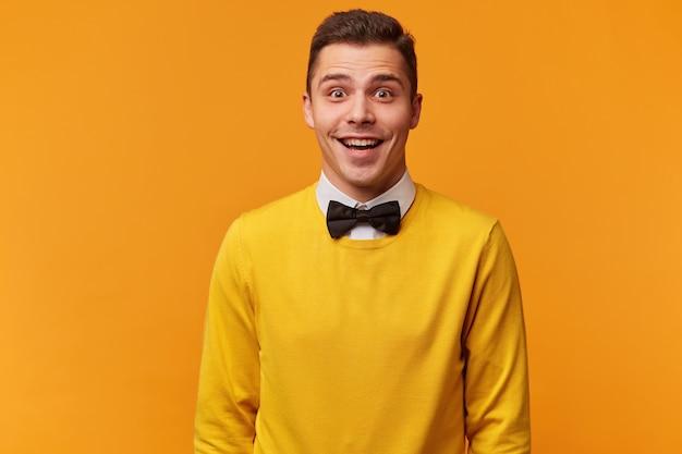 놀란 젊은 매력적인 남자의 초상화는 흰색 셔츠 위에 노란색 스웨터를 현명하게 입고 자신의 행운을 믿을 수 없습니다