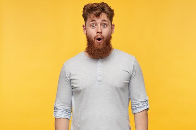 빨간 머리를 가진 놀란 젊은 수염 난된 남자의 초상화, 행복 한 표정으로 광범위 하 게 미소. 노란색에 즐거운 빨간 머리 남자의 초상화