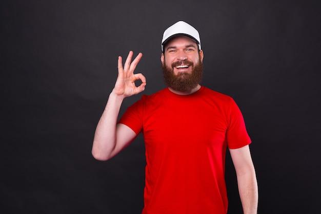 Портрет удивленного молодого бородатого улыбающегося человека, показывающего жест ок