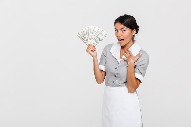 Портрет изумленной молодой экономки в форме держа веер долларовых банкнот