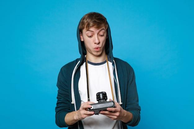 파란색 벽에 고립 된 레트로 빈티지 사진 카메라를 찾고 캐주얼 옷을 입고 놀된 젊은 남자의 초상화. 사람들이 성실한 감정 라이프 스타일 개념.