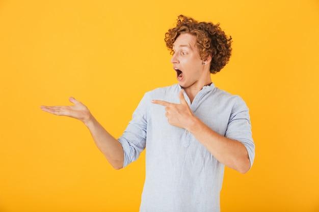 Портрет изумленного молодого человека, кричащего и держащего copyspace на ладони, изолированного на желтом фоне