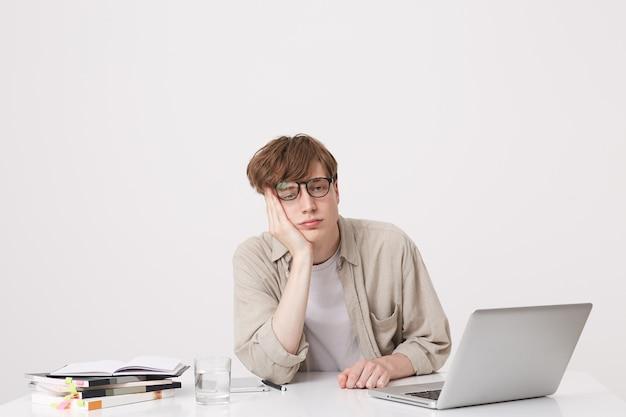 Портрет удивленного молодого человека, студента в бежевой рубашке, выглядит удивленным и учится за столом с портативным компьютером и ноутбуками, изолированными над белой стеной