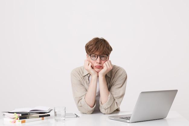 驚いた若い男の肖像画はベージュのシャツを着て驚いたように見え、白い壁に隔離されたラップトップコンピューターとノートブックでテーブルで勉強します