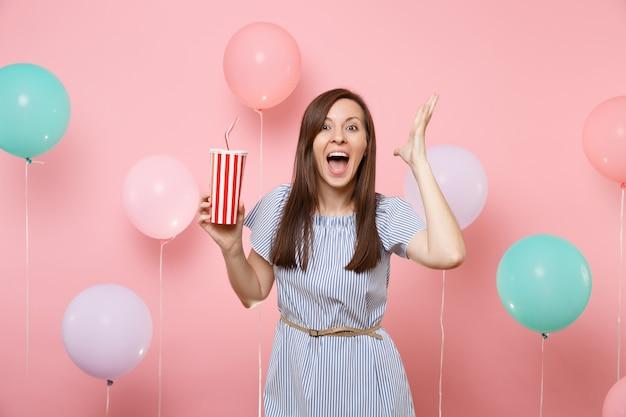 カラフルな気球とパステルピンクの背景にコーラまたはソーダのプラスチックカップを持って手を広げて開いた口を持つ青いドレスの驚いた若い女性の肖像画。誕生日の休日のパーティーのコンセプト。