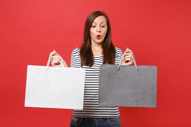줄무늬 옷을 입은 놀란 젊은 여성의 초상화는 붉은 벽 배경에서 격리된 쇼핑 후 구매한 패키지 가방을 들고 있습니다. 사람들은 진심 어린 감정, 라이프 스타일 개념입니다. 복사 공간을 비웃습니다.