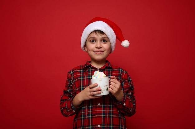 Портрет удивительного симпатичного мальчика-подростка, очаровательного ребенка в шляпе санта-клауса и клетчатой рубашке, держащего кружку горячего шоколада с зефиром, улыбается, глядя в камеру на красном фоне с копией пространства