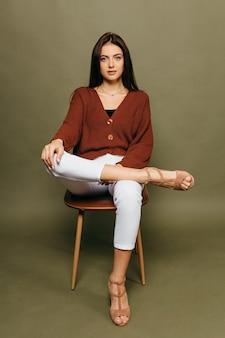 Портрет удивительной молодой девушки с красивой фигурой, сидящей на стуле на оливковом фоне в студии. фото высокого качества