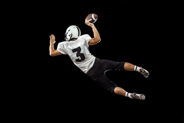 Портрет игрока в американский футбол в спортивном снаряжении, изолированном на черном