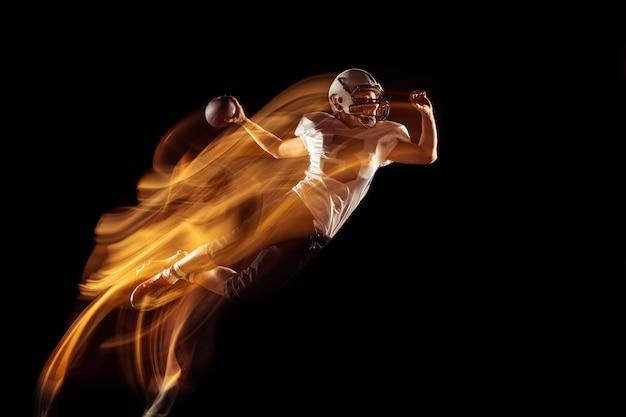 暗いスタジオの背景に分離されたスポーツ用品のアメリカンフットボール選手の肖像画。