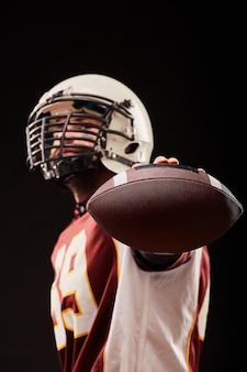 Портрет игрока в американский футбол, показывая мяч на черном фоне