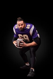 Портрет игрока в американский футбол, бросающего мяч на черном фоне