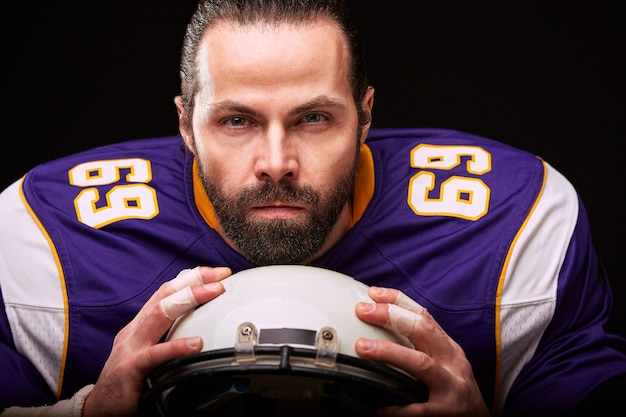 手にヘルメットを持つアメリカンフットボール選手の肖像画が黒い背景にクローズアップ