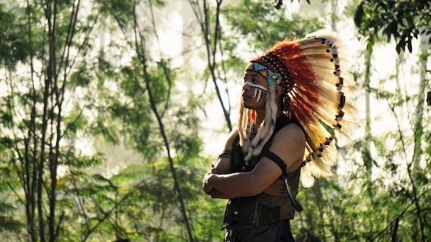 森に立っているアメリカインディアンの肖像画。