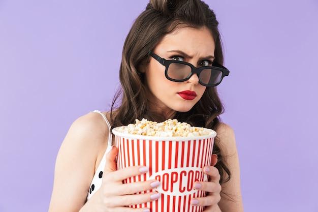 복고풍 폴카 도트 드레스와 3d 안경을 쓴 미국 핀업 여성의 초상화, 보라색 벽에 격리된 영화를 보면서 팝콘이 든 양동이를 들고