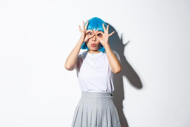 青いかつらで面白がって美しいアジアの女の子の肖像画、驚きと手眼鏡を通して見て、立っています。