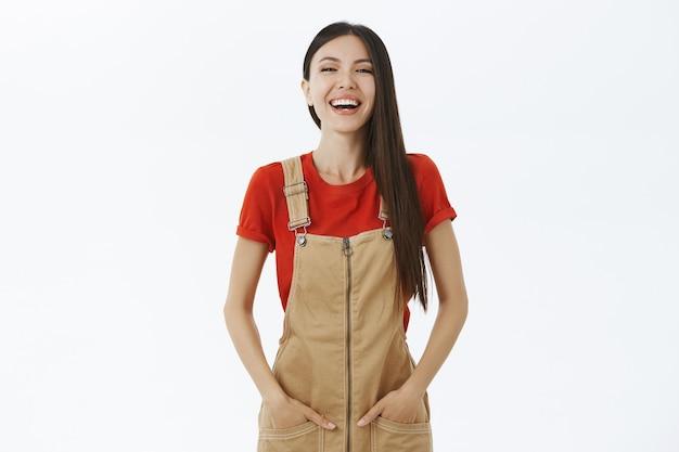 Портрет удивленной беззаботной и оптимистичной молодой привлекательной азиатской девушки с темными волосами в коричневом комбинезоне, держащей руки в карманах