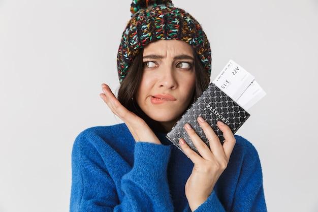 Портрет забавной женщины в зимней шапке, держащей паспорт и проездные билеты стоя, изолированной на белом