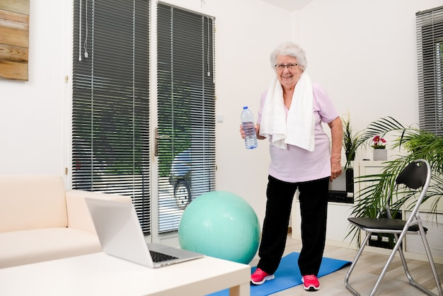 집에서 스포츠 피트니스를 하고 미네랄 워터 병을 들고 활동적이고 역동적인 노인 여성의 초상화