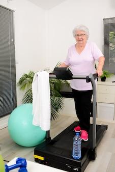 러닝머신 위를 걷는 집에서 스포츠 피트니스를 하는 활동적이고 역동적인 노년 여성의 초상화