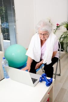 집에서 스포츠 피트니스를 하는 활동적이고 역동적인 노인 여성의 초상화