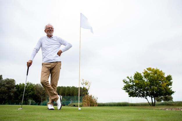 Портрет активного старшего мужчины, играющего в гольф на поле для гольфа и наслаждающегося свободным временем на открытом воздухе.