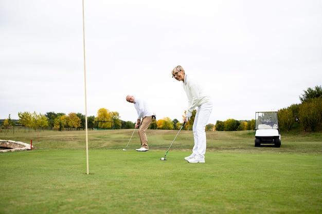 Портрет активной пожилой женщины, играющей в гольф на поле для гольфа и наслаждающейся свободным временем на открытом воздухе.