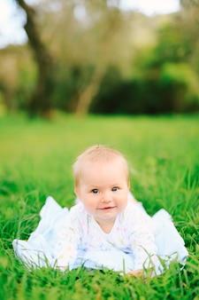 Портрет очаровательной девочки, лежащей на траве в парке. фото высокого качества