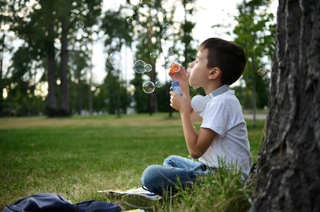 愛らしい陽気で美しいかわいい小学生の少年の肖像画は、クラスの合間にレクリエーションを楽しんだり、シャボン玉を吹いたり、都市公園の緑の芝生に座ったりします