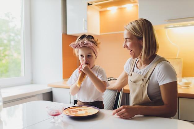 사랑스러운 엄마와 딸이 함께 부엌에서 딸 준비의 초상화.