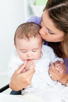 Портрет очаровательной матери, целуя ее ребенка в кухне