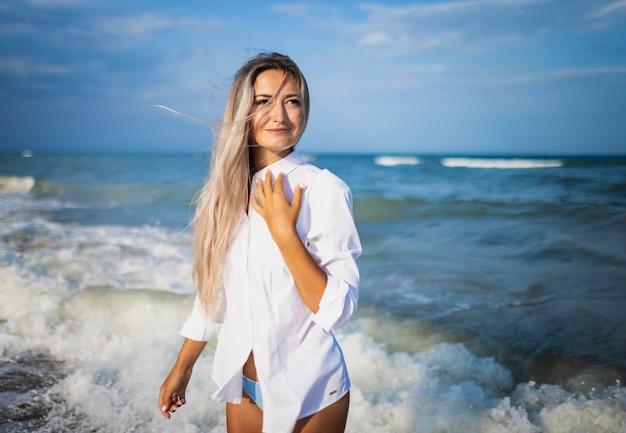 부드러운 파란색 수영복과 밝은 흰색 셔츠를 입은 사랑스러운 날씬한 소녀의 초상화, 거품 파도와 구름 한 점 없는 맑은 하늘이 있는 푸른 바다 배경